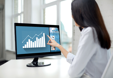 dedo señalando: negocio, la gente, la tecnología y estadísticas concepto - cerca de la mujer que señala el dedo para trazar el monitor de la computadora en la oficina