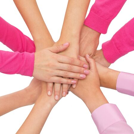 young girls breast: feminism, women power and breast cancer awareness concept - close up of women hands on top of each other over white background