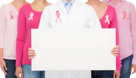 cancer symbol: healthcare, people and medicine concept - close up of women in shirts with pink breast cancer awareness ribbons and blank white board over white background