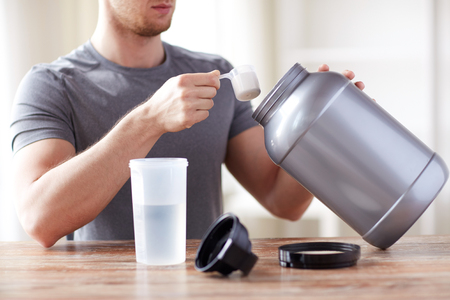 whey: sport, fitness, healthy lifestyle and people concept - close up of man with jar and bottle preparing protein shake