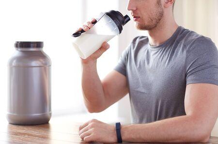 sport, fitness, gezonde levensstijl en mensen concept - close-up van de mens in de fitness armband met pot en drinkfles proteïne shake Stockfoto