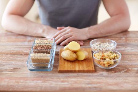 gesunde Ernährung, Diät und Menschen Konzept - Nahaufnahme von männlichen Händen mit kohlenhydratreiche Lebensmittel auf dem Tisch