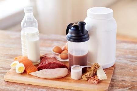 barra de cereal: deporte, fitness, estilo de vida saludable, la dieta y el concepto de la gente - cerca de pescados proteína natural y aditivo sobre la mesa de madera