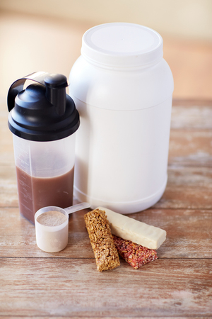 casein: sport, fitness, diet and food concept - close up of jar, protein shake bottle and muesli bars on wooden table