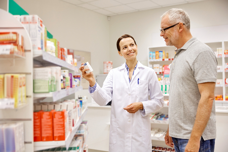 medicine, pharmaceutics, health care and people concept - happy pharmacist showing drug to senior man customer at drugstore