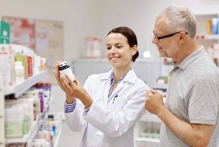 la medicina, la farmacia, la atención de la salud y la gente concepto - farmacéutico feliz mostrando medicamento para el cliente hombre mayor en farmacia Foto de archivo