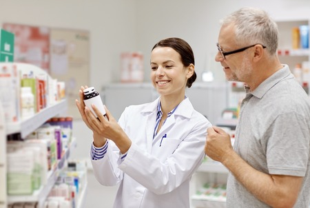 customer care: medicine, pharmaceutics, health care and people concept - happy pharmacist showing drug to senior man customer at drugstore