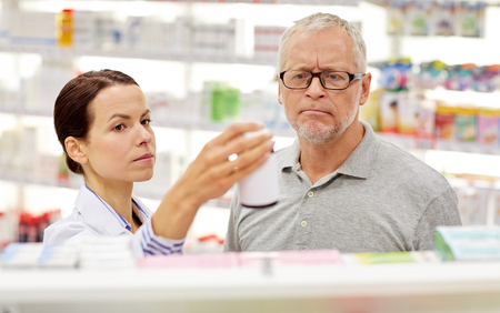health care and medicine: medicine, pharmaceutics, health care and people concept - pharmacist showing drug to senior man customer at drugstore