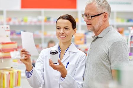 medicina: la medicina, la farmacia, la atención de la salud y la gente concepto - farmacéutico feliz y clientes hombre mayor con la droga y receta en la farmacia
