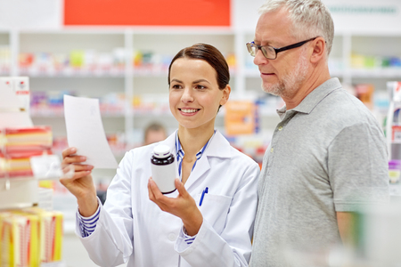 drug: medicine, pharmaceutics, health care and people concept - happy pharmacist and senior man customer with drug and prescription at drugstore