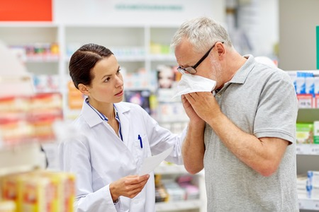 medicine, pharmaceutics, health care and people concept - pharmacist and sick senior man with flu blowing nose at pharmacy