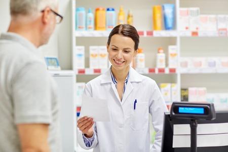 pharmaceutics: medicine, pharmaceutics, health care and people concept - pharmacist reading prescription and senior man at drugstore cash register