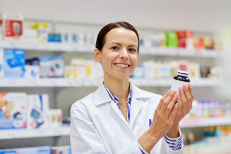 health care and medicine: medicine, pharmaceutics, health care and people concept - happy female pharmacist with drug jar at pharmacy Stock Photo