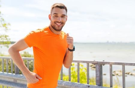 fitness, deporte, la gente, la tecnología y el concepto de estilo de vida saludable - hombre joven sonriente con el reloj de la frecuencia cardíaca se ejecuta en la playa del verano