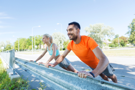 outdoor fitness: fitness, sport, training and healthy lifestyle concept - close up of happy couple doing push-ups outdoors