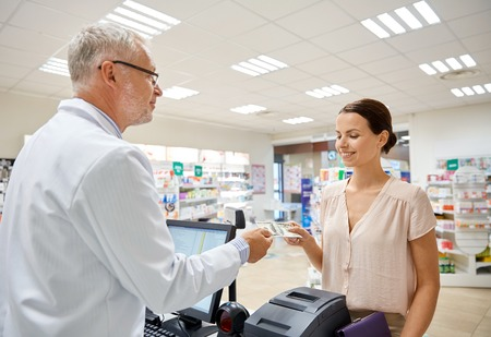 pharmaceutics: medicine, pharmaceutics, health care and people concept - smiling woman with wallet giving money to senior man pharmacist at drugstore cash register
