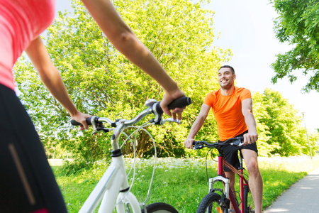 cycler: fitness, sport, people and healthy lifestyle concept - close up of happy couple riding bicycle outdoors at summer Stock Photo