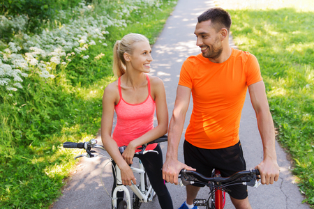 summer sport: fitness, sport, people and healthy lifestyle concept - happy couple riding bicycle outdoors at summer