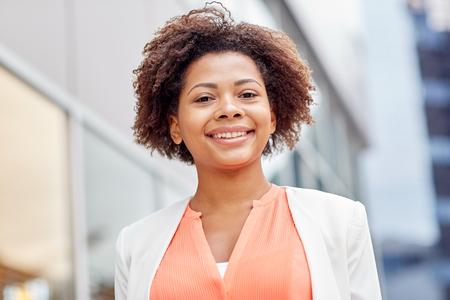 mujeres elegantes: negocios y concepto de la gente - sonriente joven empresaria afroamericana en la ciudad Foto de archivo