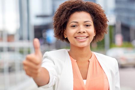 비즈니스, 성공, 제스처 및 사람들이 개념 - 도시에서 엄지 손가락을 보여주는 젊은 미소 흑인 미국 사업가