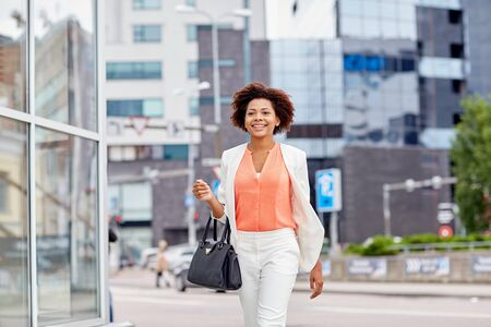 happy worker: business and people concept - young smiling african american businesswoman in city Stock Photo