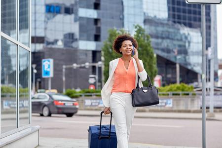 viajes, viaje de negocios, la gente y la tecnología concepto - joven mujer afroamericana feliz con bolsa de viaje caminando por calle de la ciudad y se invita a teléfono inteligente