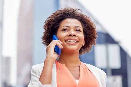 mujer trabajadora: negocio, la comunicación, la tecnología y el concepto de la gente - joven sonriente africano americano de negocios que invita al teléfono inteligente en la ciudad Foto de archivo