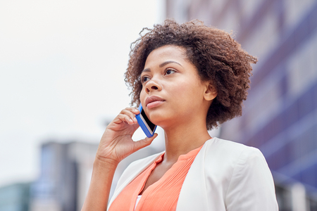 call: business, communication, technology and people concept - young african american businesswoman calling on smartphone in city
