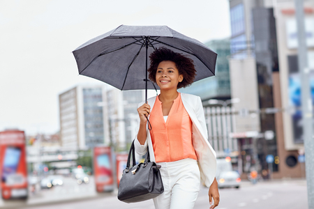 umbrella: business and people concept - young smiling african american businesswoman with umbrella and handbag walking down city street