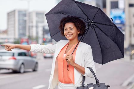 raining: viaje de negocios, el transporte y el concepto de la gente - mujer afroamericana sonriente joven con el paraguas captura de taxi en la calle de la ciudad Foto de archivo