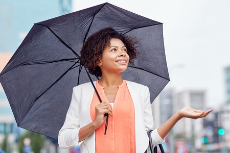 business, weather and people concept - young smiling african american businesswoman with umbrella on city street