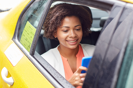taxi cab: business trip, transportation, travel, gesture and people concept - young smiling african american woman texing on smartphone in taxi at city street