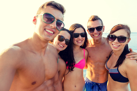 teen boys: friendship, leisure, summer, technology and people concept - group of smiling friends making selfie on beach