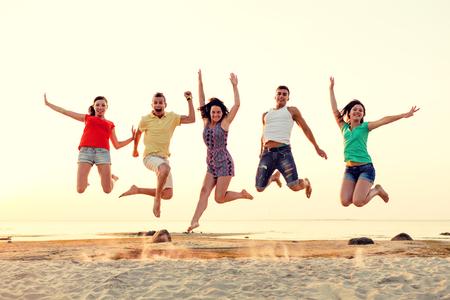 persona saltando: amistad, vacaciones de verano, las vacaciones, el partido y la gente concepto - grupo de amigos sonrientes bailando y saltando en la playa