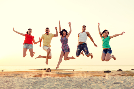 friendship, summer vacation, holidays, party and people concept - group of smiling friends dancing and jumping on beach Foto de archivo
