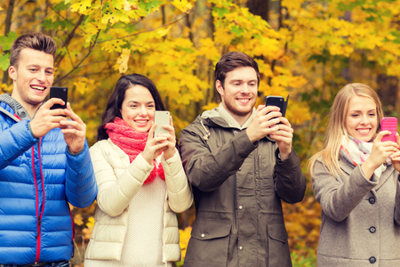 family in park: season, people, technology and friendship concept - group of smiling friends with smartphones taking picture in autumn park