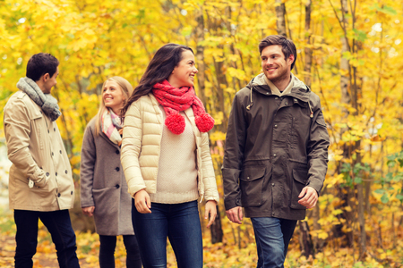 family in park: love, relationship, season, friendship and people concept - group of smiling men and women walking in autumn park