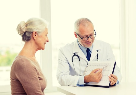 medical test: medicine, age, health care and people concept - smiling senior woman and doctor meeting in medical office