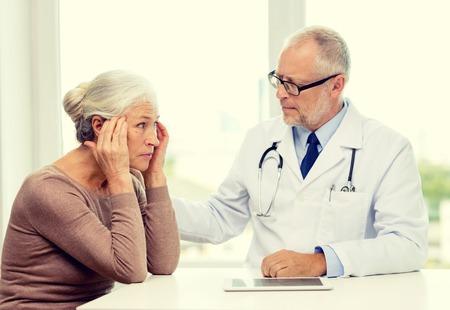 mujer decepcionada: la medicina, la edad, la salud y las personas concepto - mujer mayor y doctor con el ordenador que cumpla Tablet PC en la oficina médica