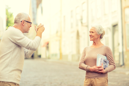 tourist guide: age, tourism, travel, technology and people concept - senior couple with map and camera photographing on street