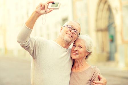 edad, turismo, viajes, tecnología y concepto de la gente - pareja senior con cámara que toma Autofoto en la calle