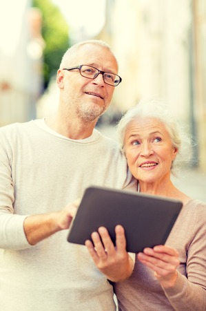 computer age: age, tourism, travel, technology and people concept - senior couple with tablet pc computer on street Stock Photo