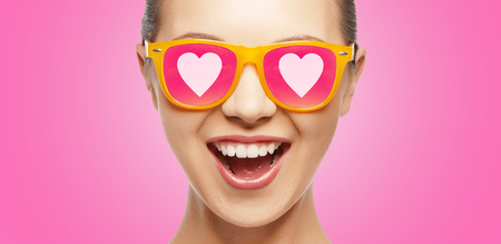 teen love: love, happiness and valentines day concept - amazed teen girl in sunglasses with hearts on pink background