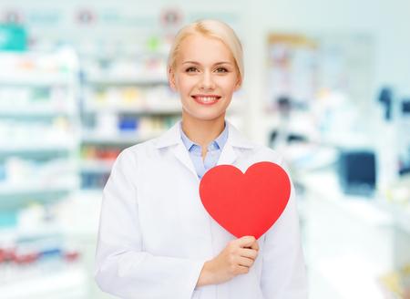 geneeskunde, farmacie, mensen, de gezondheidszorg en de farmacologie concept - happy jonge vrouw apotheker die rood hart vorm over drogisterij achtergrond