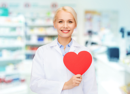 pharmacist: medicine, pharmacy, people, health care and pharmacology concept - happy young woman pharmacist holding red heart shape over drugstore background