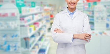medicine, pharmacy, people, health care and pharmacology concept - happy young woman pharmacist over drugstore background Reklamní fotografie