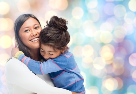 people, motherhood, family and adoption concept - happy mother and daughter hugging over blue holidays lights background Stock Photo
