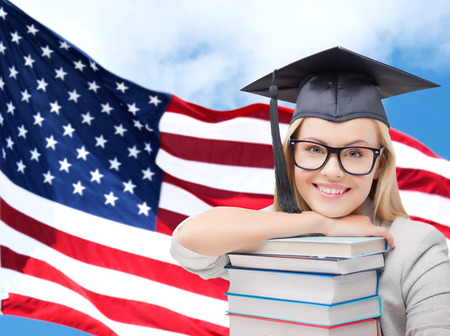 trencher: education, high school, knowledge and people concept - picture of happy student girl or woman in trencher cap with stack of books over american flag background