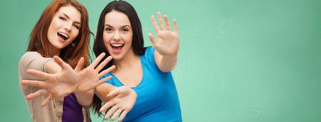 la escuela, la educación, la felicidad y el concepto de la gente - dos sonriente a muchachas del estudiante o las mujeres jóvenes que muestran sus palmas de las manos sobre el fondo pizarra verde
