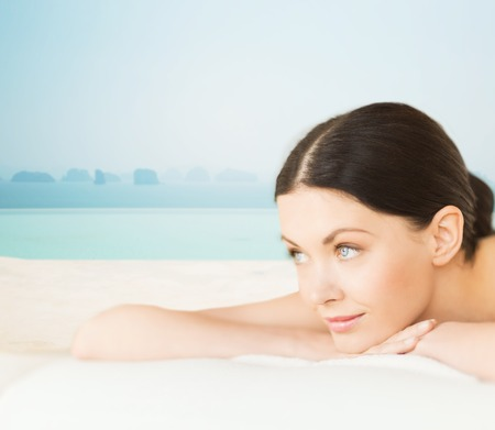 girl lying: people, beauty and body care concept - happy beautiful woman lying on massage desk at spa resort over sea and infinity pool background